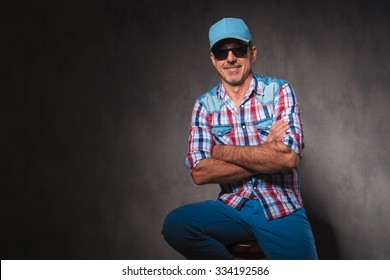 relaxed happy old casual man sitting with hands crossed in studio, wearing trucker hat