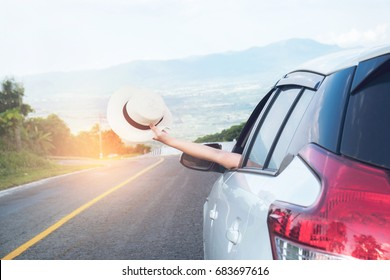 Relaxed happy traveler, Young beatiful asian gilr holding white Hat weave and Reach out of the car at sunset and beautiful view with mountain road background.
