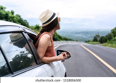 Relaxed happy traveler, Young beautiful girl wearing white hat weave Reach out of the car at sunshine and nature view with mountain road background.