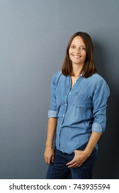 Relaxed happy woman in casual leisurewear standing with her thumb in the pocket of her jeans with a confident over a grey studio background with copy space