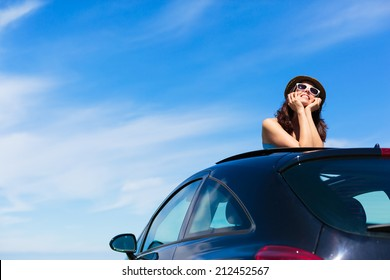 Relaxed happy woman on summer travel vacation leaning out car sunroof on blue sky background.