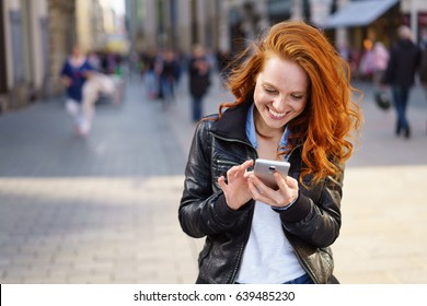 Relaxed happy woman texting on her mobile phone outdoors on an urban pedestrian street with copy space alongside her