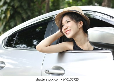 Relaxed happy young woman on summer vacation leaning out car window on nature background