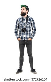 Relaxed hipster wearing black dslr camera over neck with hands in pockets. Full body length portrait isolated over white studio background.