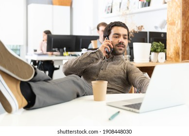 A relaxed hispanic man with mustache whith his feet on desk talking on the phone in the office.