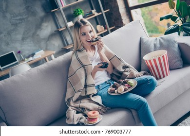 Relaxed joyful crazy hungry careless excited glad woman sitting on a couch in a living room in front of tv and eating tasty appetizing pastry donuts and popcorn