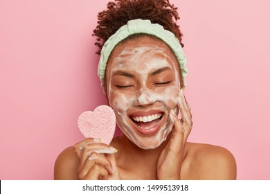 Relaxed joyful dark skinned female model washes face with soap bubbles, enjoys pampering session, keeps eyes closed from pleasure, holds cosmetic sponge, cares about body, stands naked indoor