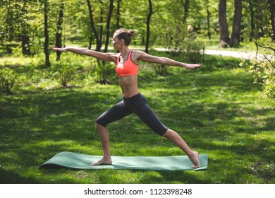 Relaxed lady is training and enjoying connection with surrounding environment. She is balancing in warrior asana while standing on mat and straighten arms. Solitude in calming nature concept