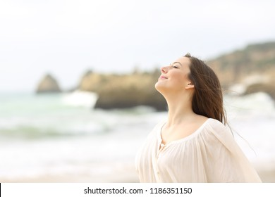 Relaxed lady in white breathing deep fresh air on the beach