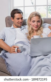 Relaxed loving young couple with coffee cups using laptop on sofa at home