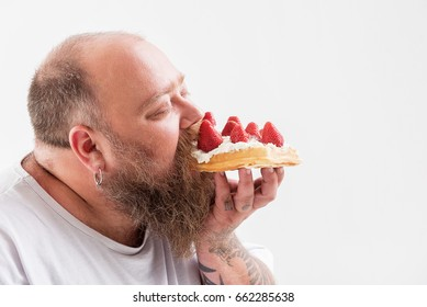 Relaxed male fatso eating tasty cake