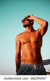 Relaxed man at the beach. Healthy tanned male sunbathing