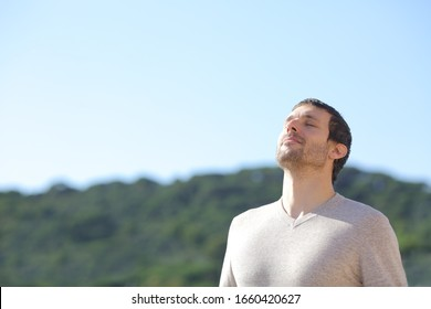 Relaxed man breathing fresh air near the mountains with a blue sky in the background