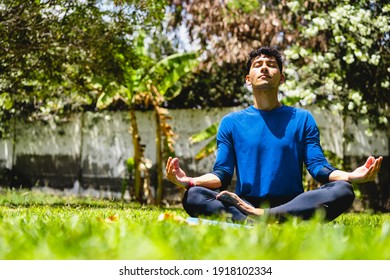 RELAXED MAN DOING EXERCISE AND MEDITATION YOGA ON NATURE OUTDOOR