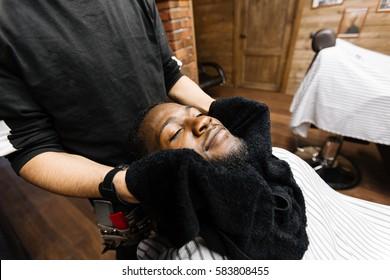 Relaxed man enjoying hot-towel mask before shaving