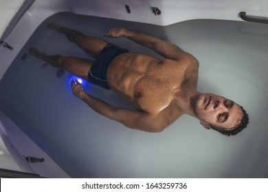 Relaxed man is floating in a sensory deprivation tank. He is very relaxed. Welness and Spa concept.