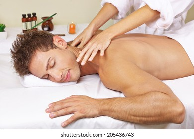 Relaxed man getting thai massage for his back in a day spa