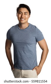 Relaxed man in a light blue tshirt standing against a white background looking at camera.