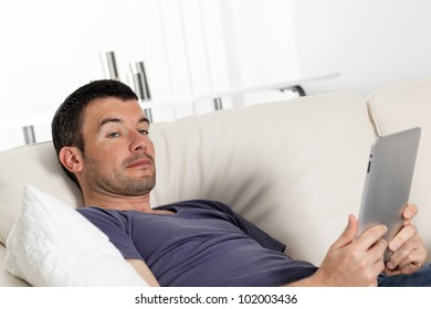 relaxed man on sofa with tablet