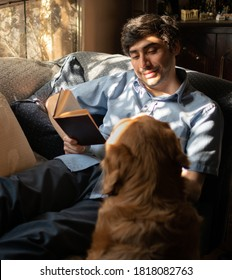 A relaxed man reading a book lying on a sofa next to a dog. Young smiling latin with black hair and a light blue shirt enjoying.