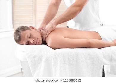 Relaxed man receiving back massage in wellness center