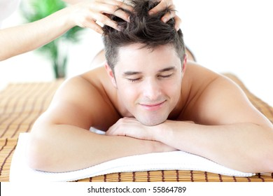 Relaxed man receiving a head massage in a Spa center