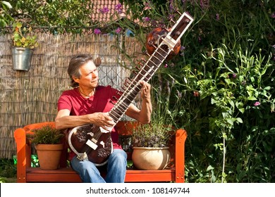 relaxed man sitting in his garden and playing sitar
