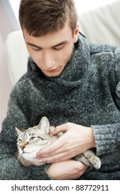 Relaxed man sitting on armchair holding and petting pet cat