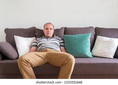 relaxed man sitting on the sofa and looking at the camera