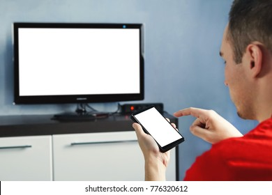 Relaxed man with smartphone connected to a tv. Blank screen white screen. The form for information. TV screen without information and content. Using a smartphone to transmit information to the TV