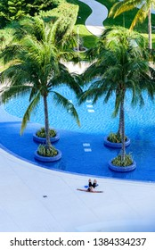 relaxed man with sportswear outside a pool with palm trees inside, in a hotelier complex seen from above