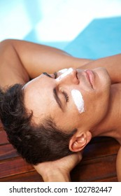 Relaxed man sunbathing with sunscreen on his nose and cheeks