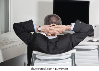 Relaxed manager at his desk leaning back in the office