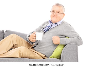 Relaxed mature man laying on sofa and drinking tea isolated on white background