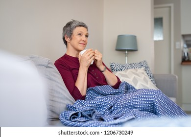 Relaxed mature woman enjoying tea sitting with blanket on a comfortable couch. Senior woman holding coffee mug sitting on sofa and thinking. Thoughtful lady sitting comfortably at home in autumn.