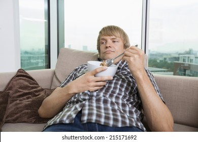 Relaxed mid-adult man with bowl of cereal in living room at home