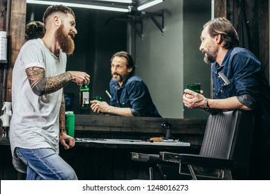 Relaxed middle aged bearded men having a pleasant friendly talk in barbershop while enjoying their beer