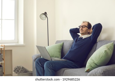Relaxed middle-aged businessman took a break from work sitting on a comfortable sofa with a laptop and putting his hands behind his head. Concept is no stress, fatigue and relaxation.
