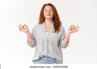 Relaxed middle-aged carefree redhead woman exercise yoga breathing practice gather patience release stress smiling close eyes inhale fresh air standing lotus nirvana zen pose meditating happily