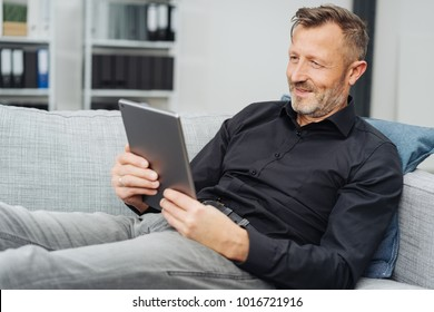 Relaxed middle-aged man reading an e-book on his tablet pc as he sits back on a comfortable sofa at home