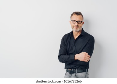Relaxed middle-aged man wearing glasses standing with folded arms over a white background looking at the camera