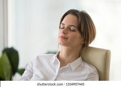 Relaxed mindful woman with calm happy face resting on comfortable office chair after work breathing fresh air, taking break for relaxation meditation feeling no stress for mental emotional health