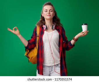 relaxed modern student woman in a red shirt with backpack and headphones with coffee cup doing yoga isolated on green