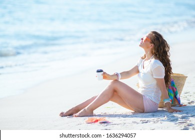 relaxed modern woman in white t-shirt and pink shorts with coffee cup sitting on the seashore.