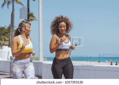 Relaxed multiethnic sportive women working out together on promenade and running in relaxation chatting in sunlight.