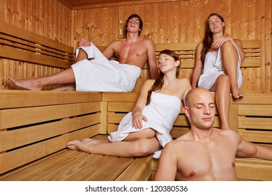 Relaxed people sitting together in a sauna with their eyes closed
