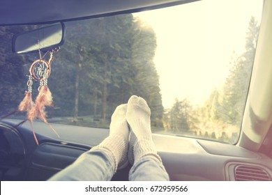 Relaxed person with feet on dashboard during car trip