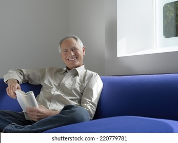 Relaxed portrait of a senior man sitting with a book looking to camera in a contemporary interior