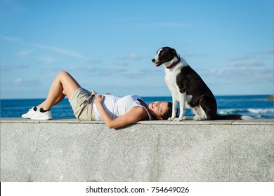 Relaxed pregnant woman resting and enjoying tranquility towards the sea with her dog.