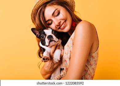 Relaxed red-haired girl embracing puppy on yellow background. Studio portrait of white appealing woman chilling with dog.